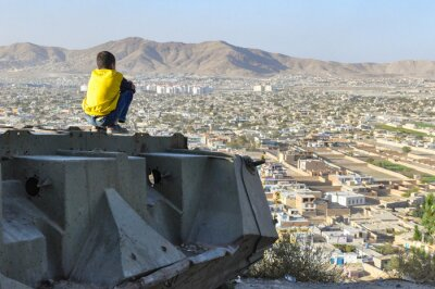 Bild Boy sitting on Destroyed Tank on the hills over Kabul City in Afghanistan