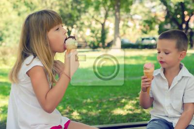 Bruder und Schwester essen Eis am sonnigen Sommertag