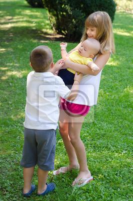 Bruder und Schwester spielen mit kleinen Baby Bruder
