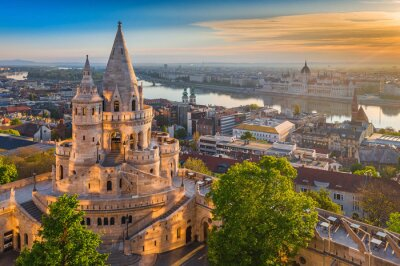 Bild Budapest, Hungary - Beautiful golden summer sunrise with the tower of Fisherman's Bastion and green trees. Parliament of Hungary and River Danube at background. Blue sky.