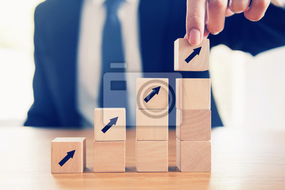 Bild Business concept growth success process, Close up Businessman hand arranging wood cube with arrow stacking as step stair.