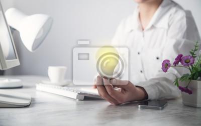 Bild Business girl holding light bulb in office desk. Idea