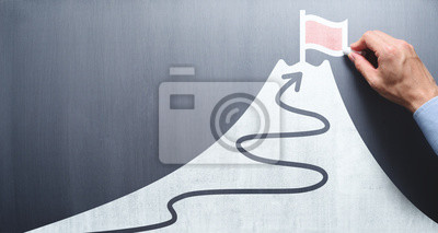 Bild Business goal and success concept. Businessman drawing flag and mountain on chalkboard.