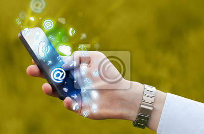 Bild Business man holding smart phone with media icons