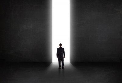 Bild Business-Person Blick auf Wand mit Licht Tunnel-Öffnung