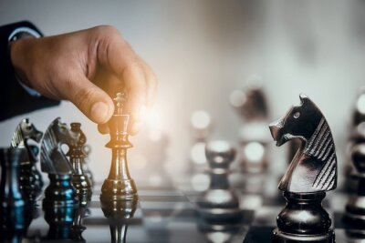 Bild Businessman moving chess piece and think strategic to win game. Chess board game concept for ideas and competition and strategy, business success concept
