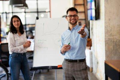 Bild Businessman present his idea to working team. Young happy man presenting businessplan.