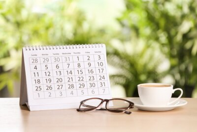Bild Calendar, glasses and cup of coffee on wooden table against blurred background