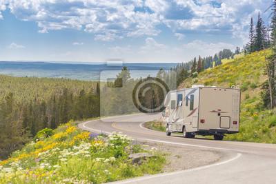 Bild Camper Driving Down Road in der schönen Landschaft unter Kiefern und Blumen.