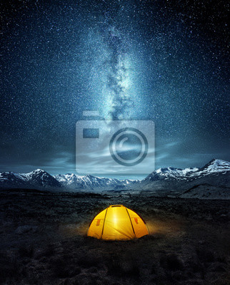 Bild Camping in the wilderness. A pitched tent under the glowing  night sky stars of the milky way with snowy mountains in the background. Nature landscape photo composite.
