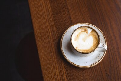 Bild Cappuccino in rustic cup and dish on a brown coffee shop table. Top view, flat lay.