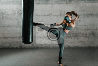 Bild Caucasian woman in sportswear and with boxing gloves kicking bag in the gym. Full length. Wall in background.