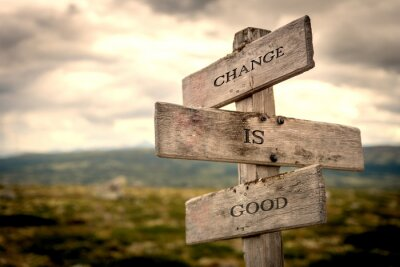 Bild Change is good quote on wooden signpost in nature with moody background. Motivational, move on, changes, choice, choices concept.