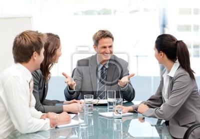 Cheeful Manager im Gespräch mit seinem Team bei einem Treffen
