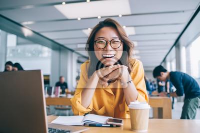 Bild Cheerful female freelancer in workspace