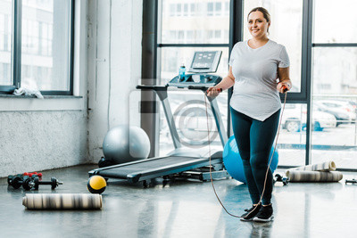 Bild cheerful plus size woman standing with jumping rope in gym