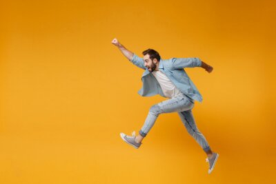 Bild Cheerful young bearded man in casual blue shirt posing isolated on yellow orange background studio portrait. People lifestyle concept. Mock up copy space. Jumping with outstretched hand like Superman.