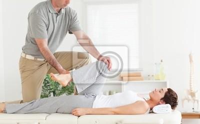 Chiropraktiker erstreckt Frau Arm