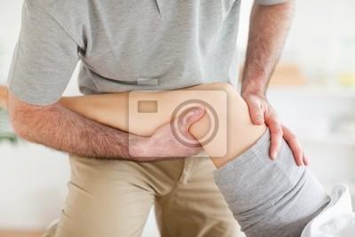 Chiropraktiker massiert Knie einer Frau