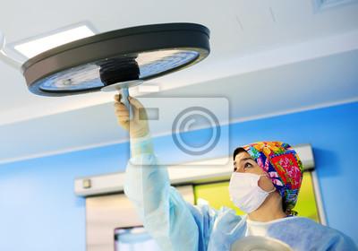 Bild Chirurg stellt die Lampe im Operationssaal ein