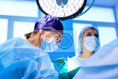 Bild Chirurgen, die einen Patienten im Operationsraum laufen lassen