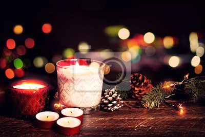 Bild Christmas background - Christmas candle and rustic decoration on wood table with christmas lights background in night party. vintage color style.