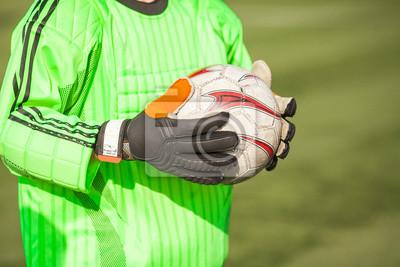 Close up der Hände des Torhüters halten einen Fußball.