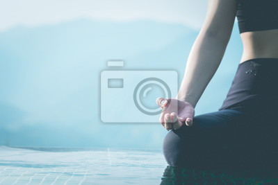 Close up Hand of woman practice yoga Lotus pose on the pool above the Mountain peak in the morning in front of beautiful nature views in SAPA vietnam,Feel so comfortable and relax