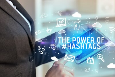 Close-up Of A Person Using Social Networking with THE POWER OF #HASHTAGS inscription