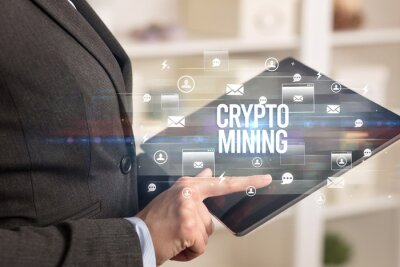 Close-up of a tablet searching CRYPTO MINING inscription, modern technology concept