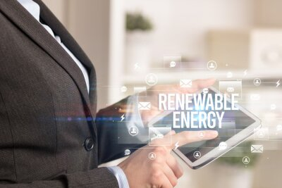 Close-up of a tablet searching RENEWABLE ENERGY inscription, modern technology concept