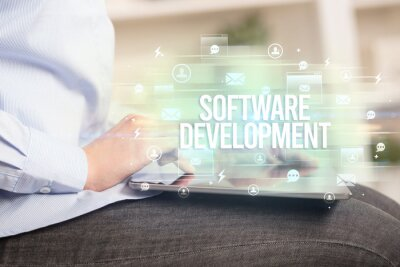 Close-up of a tablet searching SOFTWARE DEVELOPMENT inscription, modern technology concept