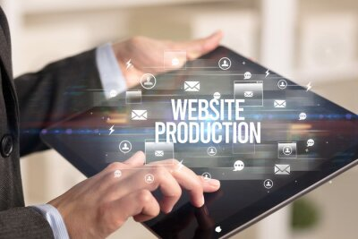 Close-up of a tablet searching WEBSITE PRODUCTION inscription, modern technology concept