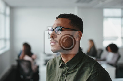Bild Close-up of a young african american business man entrepreneur wearing eyeglasses contemplating in office