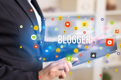 Close up of business person playing multimedia with social media icons and BLOGGER inscription