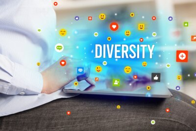 Close up of business person playing multimedia with social media icons and DIVERSITY inscription
