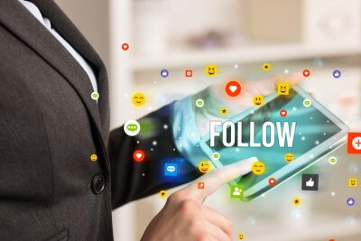 Close up of business person playing multimedia with social media icons and FOLLOW inscription
