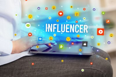 Close up of business person playing multimedia with social media icons and INFLUENCER inscription