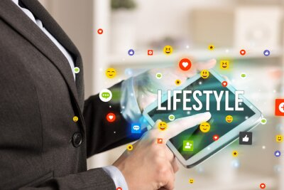 Close up of business person playing multimedia with social media icons and LIFESTYLE inscription