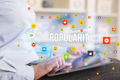 Close up of business person playing multimedia with social media icons and POPULARITY inscription