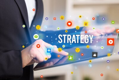 Close up of business person playing multimedia with social media icons and STRATEGY inscription