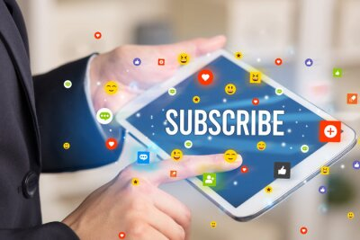 Close up of business person playing multimedia with social media icons and SUBSCRIBE inscription