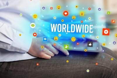 Close up of business person playing multimedia with social media icons and WORLDWIDE inscription