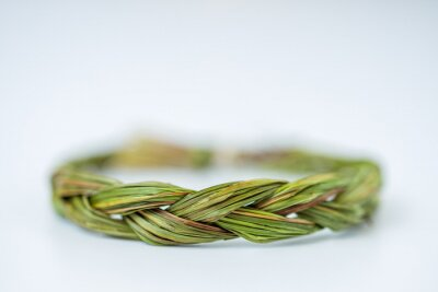Bild Close up of middle of green fresh sweetgrass braid tied in a circle isolated on white background