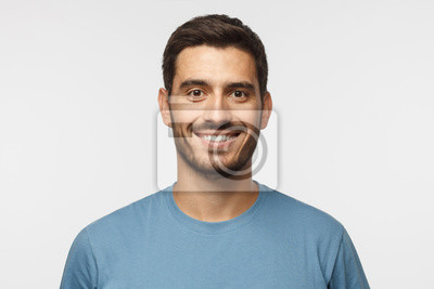 Bild Close up portrait of young smiling handsome guy in blue t-shirt isolated on gray background