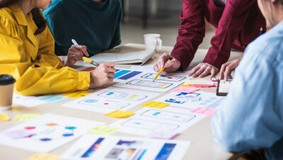 Bild Close up ux developer and ui designer brainstorming about mobile app interface wireframe design on table with customer breif and color code at modern office.Creative digital development agency.