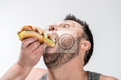 Bild close up view of overweight man in tank top eating hot dog isolated on white