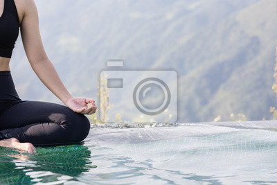 Close up woman practice yoga Lotus pose on the pool above the Mountain peak in the morning in front of beautiful nature views in SAPA vietnam,Feel so comfortable and relax in holiday