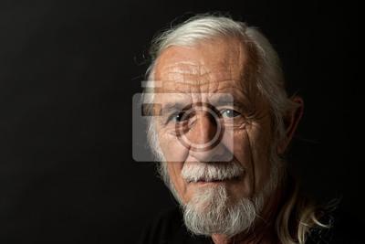 Bild Closeup low key studio portrait of beautiful gray hair old man looking at the camera. Horizontally.