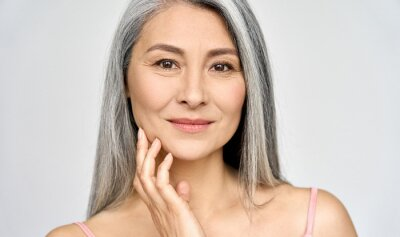 Bild Closeup portrait of gorgeous happy middle aged mature asian woman, senior older 50 year lady looking at camera touching her face isolated on white. Ads of lifting anti wrinkle skin care treatment.